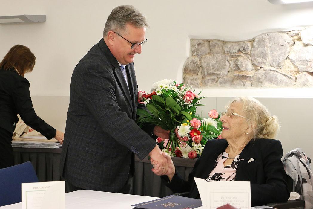 Bürgermeister Zimmermann gratuliert der im Rollstuhl sitzenden Gerda Berger