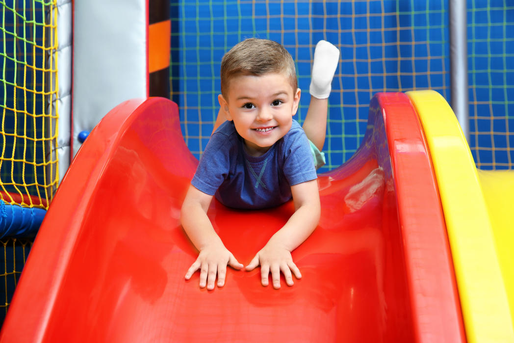 Little boy riding on slide in entertainment center ©Africa Studio - stock.adobe.com